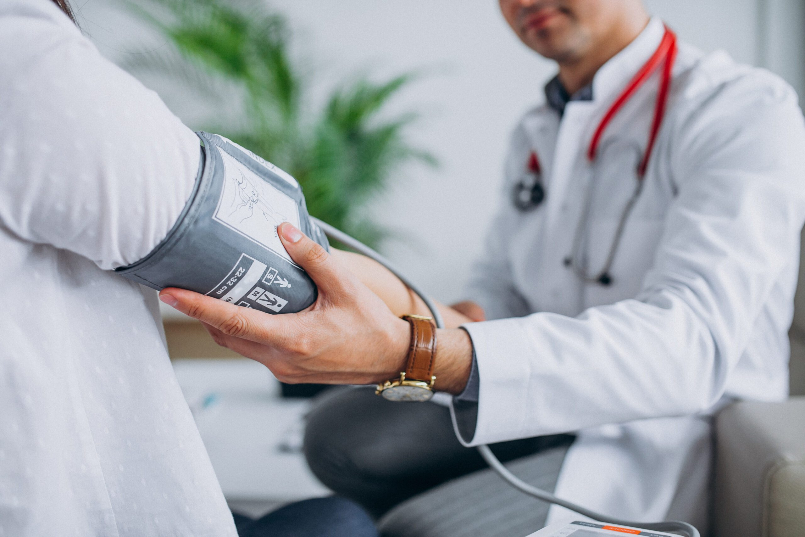 Young male psysician with patient measuring blood pressure